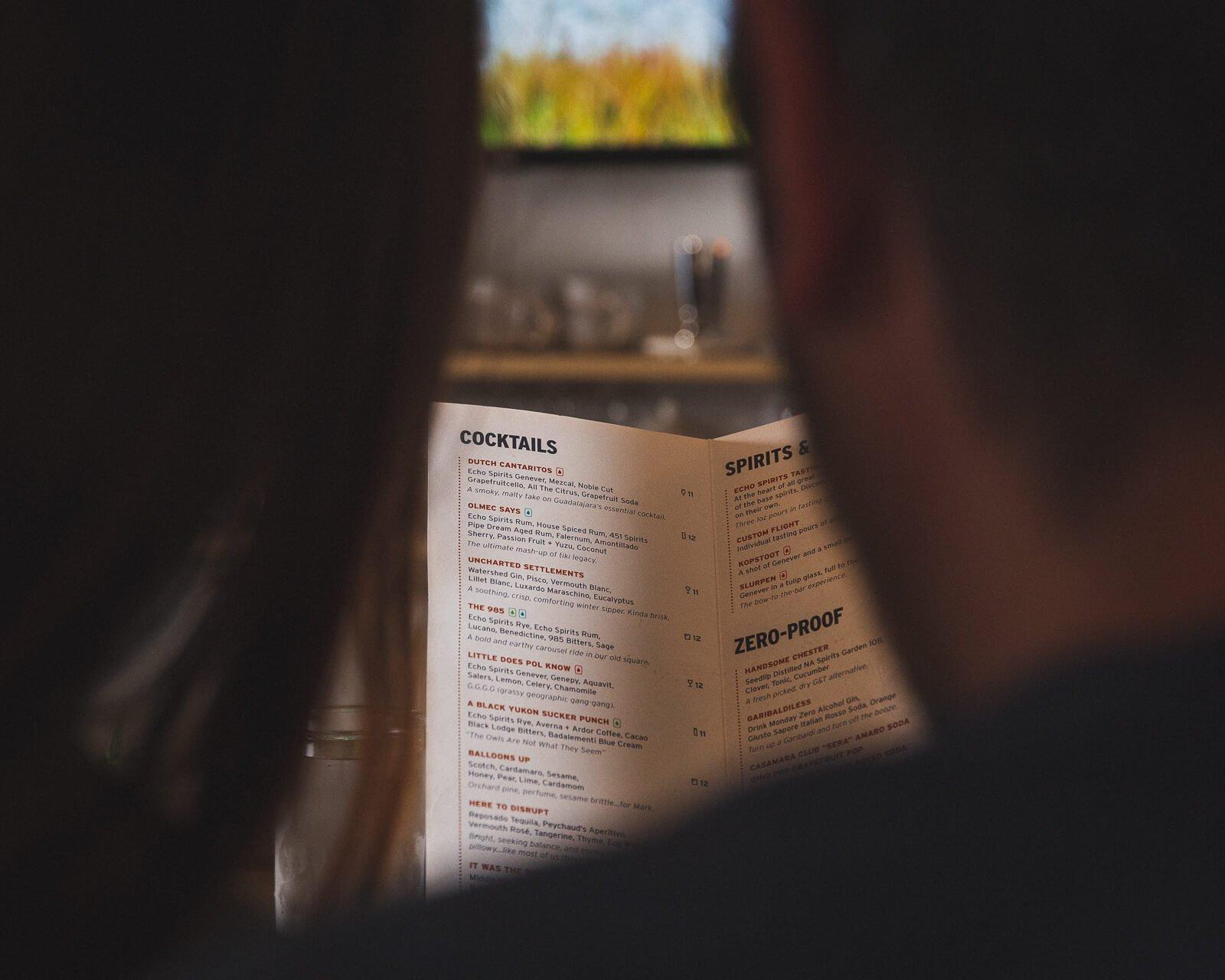two guests read a menu at the bar at echo spirits