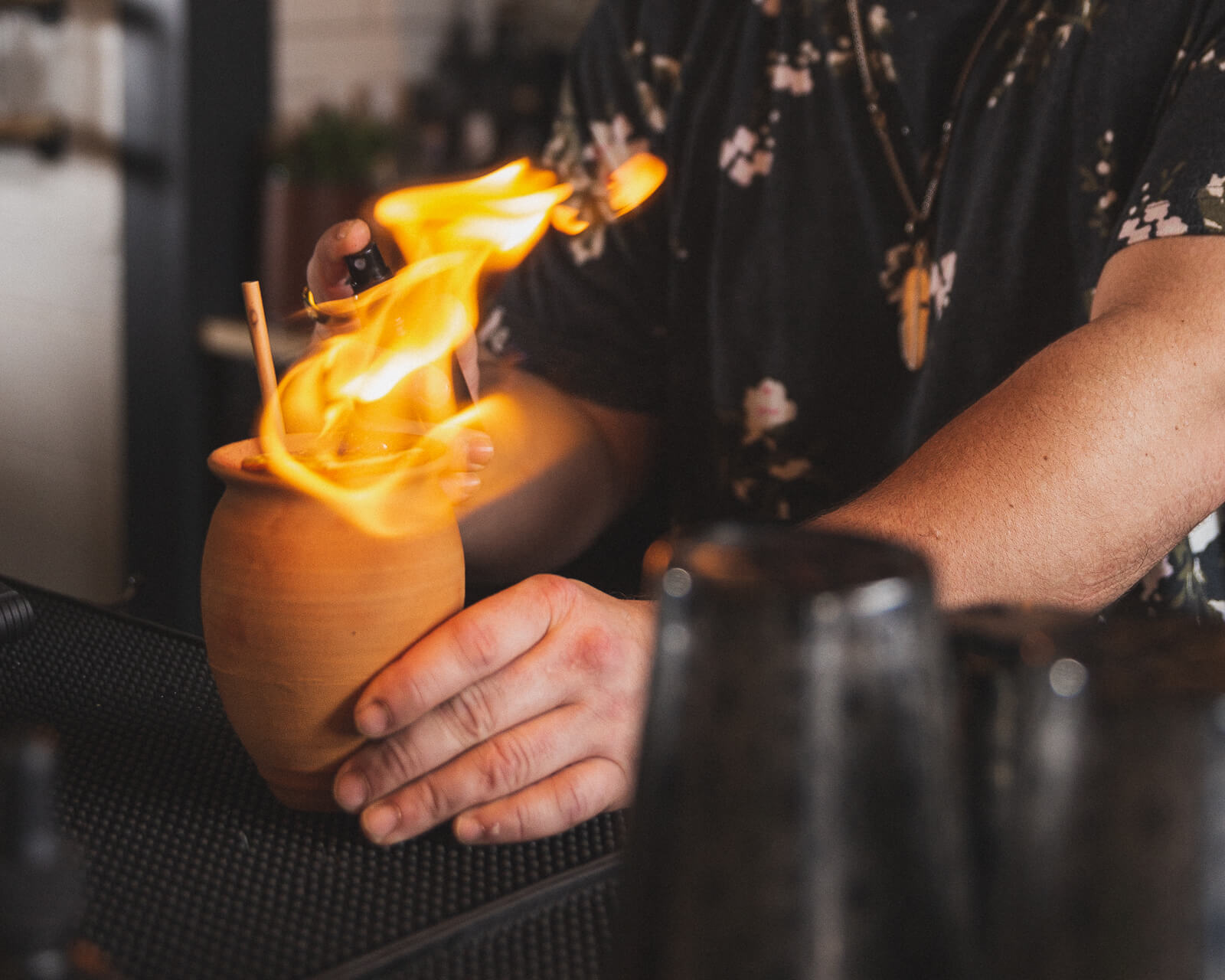 The bartender lights a flamed garnish for a high end drink at the bar at echo spirits