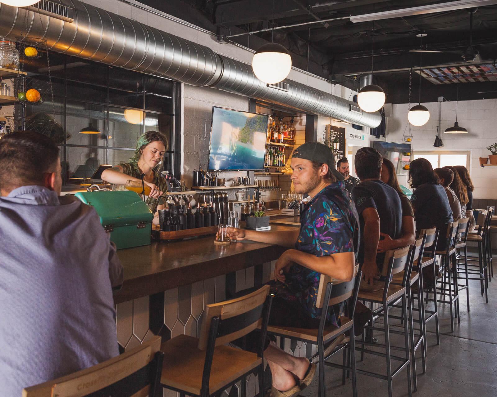 Two guests talking at a full bar