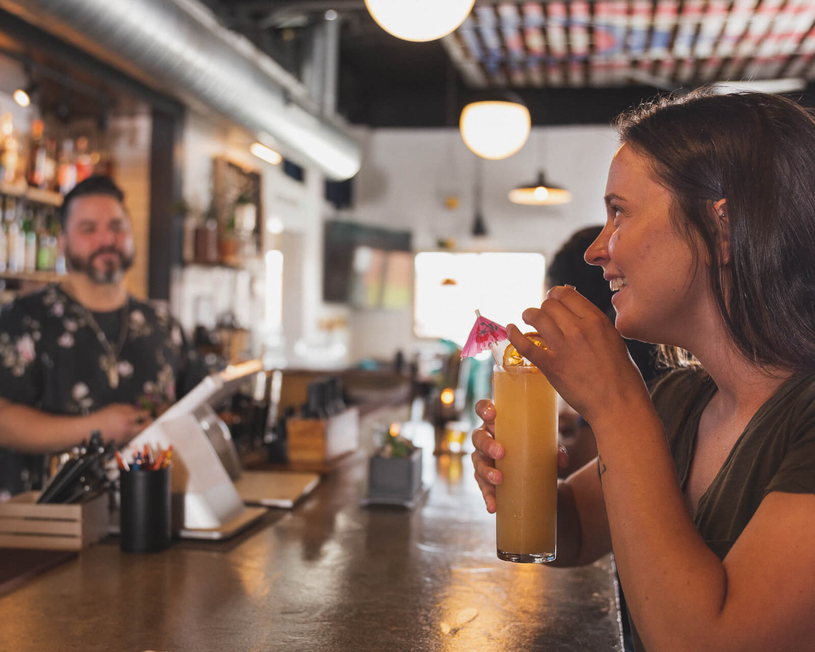 a bartender is serving a guest a tiki drink at the bar